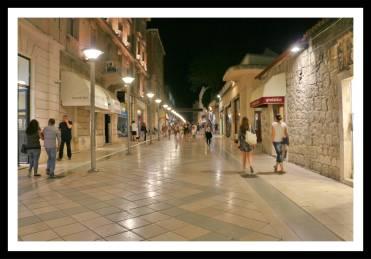 Rua de comércio, a Marmontova fica bem iluminada à noite