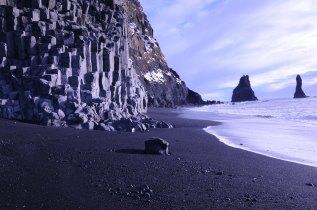 Que praia inofensiva! Observe o paredão de rochas